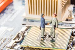 Information Technology security or IT success concept. Two miniature businessmen IT managers shaking hands while standing on CPU a stock photos