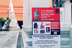 Information warning sign board to suit and respect the place at Wat Mahathat in Bangkok, Thailand Stock Photos