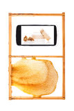 Information on your fingertips. All information on your fingertips. Honeycomb and smartphone with royal jelly cosmetics. Information age concept royalty free stock photo