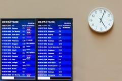 Informationsbräde om flygplats, nära klockan med händer, som visar fyra minuter förbi fem, flygschema royaltyfri bild