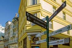 Informationsgatan undertecknar Karlovy varierar in på byggnadsbakgrunden för republiktown för cesky tjeckisk krumlov medeltida ga Royaltyfri Bild