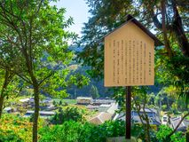 Informative sign of japanesse letter with a beautiful landscape of the mountain with some houses, in a gorgeous blue sky Royalty Free Stock Images