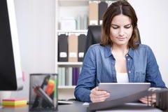 Informazioni della lettura della donna di affari sulla sua compressa Fotografie Stock