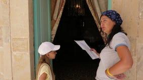 Informazioni della lettura della mamma in carta all'adolescente della figlia vicino alla porta nella casa stock footage