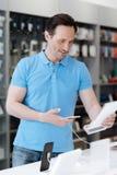 Informazioni maschii curiose della lettura del cliente sul telefono al deposito di elettronica Fotografia Stock