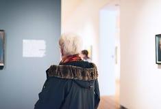 Informazioni senior della lettura della donna di materiale illustrativo nella stanza del museo Immagine Stock Libera da Diritti