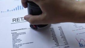 Informe al por menor aprobado, mano que sella el sello en el documento oficial, estadísticas almacen de video