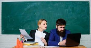 Informe anual Profesor y supervisor que trabajan junto en sala de clase de la escuela Educador de la escuela con el ordenador por fotos de archivo libres de regalías