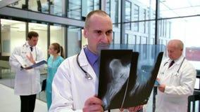 Informe de examen de la radiografía del doctor en pasillo almacen de metraje de vídeo