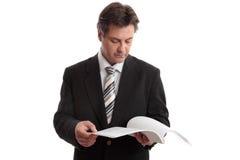 Informe de la lectura del hombre de negocios   Imagen de archivo