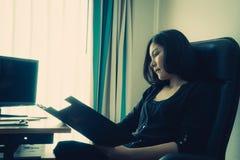 Informe de ventas femenino de la lectura del encargado de compañía en oficina fotos de archivo