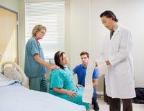 Informe del doctor Explaining Fetal Monitor a embarazada fotos de archivo libres de regalías