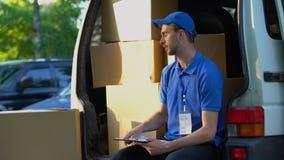 Informe joven y sonrisa de la distribución del paquete de la escritura del repartidor, sentándose en furgoneta metrajes