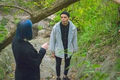 Informell flicka med blått hår och en man med blek hud på gå för gata fotografering för bildbyråer