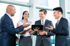 Informelle Geschäftsleute mit der Tabellencomputerdiskussion stockbild