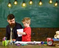Informelles Bildungskonzept Kunstlektion im Kindergarten Netter Junge, der Lehrer seine Zeichnung zeigt stockbilder