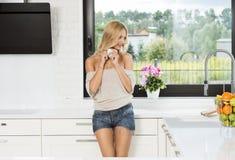 Informelles Mädchen, trinkender Kaffee in der Küche Stockfotos