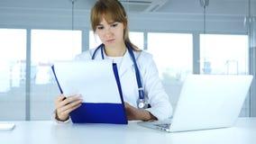 Informes médicos de lectura del paciente, diagnosis del doctor de sexo femenino joven imagen de archivo libre de regalías