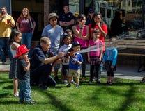 Inforni l'uomo e poco combattente di fuoco con la manichetta antincendio fotografie stock