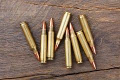 Inforni le cartucce della pallottola del fucile o del braccio su una vecchia tavola di legno Immagini Stock Libere da Diritti