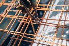 infraestrutura - mãos do trabalhador da construção que fixam as barras de aço com a haste de fio para o reforço do cimento imagem de stock royalty free