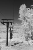 Infrared chair lift. Black and white infrared image of a ski chair lift during summer Stock Images