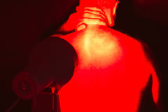 Infrared heat light therapy. Back pain. Infrared heat  light lamp therapy Royalty Free Stock Images