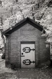 Infrared Photo of a Small Brick Building at a Cemetery Royalty Free Stock Photography
