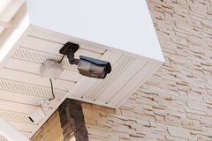 Infrared security day and night cameras. Infrared security day and night cameras on wall of house covered with lite brown decorative slate stone wall surface Stock Image