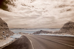 Infrared shot of badlands and road Stock Images