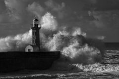 Infrared stormy waves over old lighthouse Stock Photos
