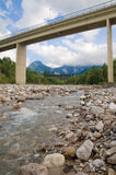 Infrastructure. Over the river and the stones. Mountains on background Royalty Free Stock Photo