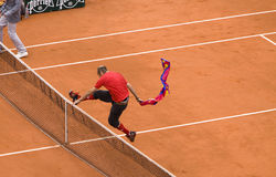 Infringer ran in on court with flag at French Op. PARIS - JUNE 7: Unidentified spectator Fan-hooligan ran onto court with flag at Tennis tournament French Open royalty free stock photography