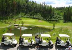 Infront de quatro carros de golfe da fonte Imagem de Stock Royalty Free