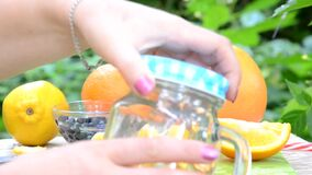woman makes Infused detox water with blueberry, orange and mint. in glass mason jar against a background of green
