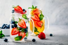 Infused detox water with blueberry, strawberry, orange and mint. Ice cold summer cocktail or lemonade. Royalty Free Stock Photography