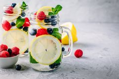 Infused detox water with lemon slice, raspberry, blueberry and mint. Ice cold summer cocktail or lemonade in mason jar. Infused detox water with lemon slice royalty free stock images