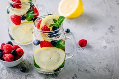 Infused detox water with lemon slice, raspberry, blueberry and mint. Ice cold summer cocktail or lemonade in mason jar. Infused detox water with lemon slice Royalty Free Stock Photos