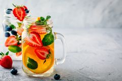 Infused detox water with orange, strawberry, blueberry and mint. Ice cold summer cocktail or lemonade. Royalty Free Stock Photography