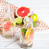 Infused flavored water with fresh fruits on white wooden background. Royalty Free Stock Photography
