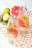 Infused flavored water with fresh fruits on white wooden background. Stock Image