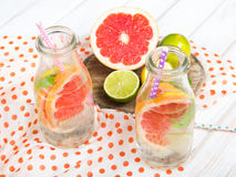 Infused flavored water with fresh fruits on white wooden background. Stock Photo