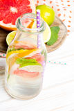 Infused flavored water with fresh fruits on white wooden background. Stock Images