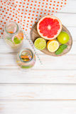Infused flavored water with fresh fruits on white wooden background. Royalty Free Stock Images