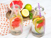 Infused flavored water with fresh fruits on white wooden background. Refreshing summer homemade detox water royalty free stock image