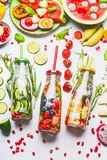 Infused water in bottles with fresh fruits, vegetables and herbs on white background with ingredients. Top view. Summer drinks. Healthy and clean detox royalty free stock image