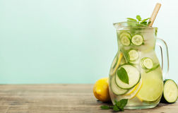 Infused water with cucumber, lemon, lime and mint. On blue background Stock Photography