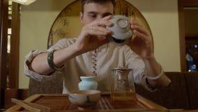 Infusión de colada principal del té verde de gaiwan a la vista delantera del cuenco de la imparcialidad almacen de video