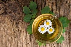 Infusión de hierbas con la manzanilla en la tabla de madera vieja Visión superior Concepto de la medicina alternativa Imágenes de archivo libres de regalías