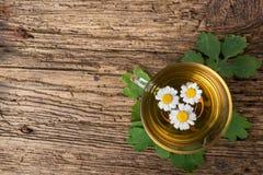 Infusión de hierbas con la manzanilla en la tabla de madera vieja Visión superior Concepto de la medicina alternativa Foto de archivo